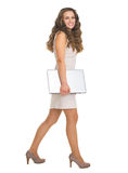 Full length portrait of young woman with laptop going sideways Royalty Free Stock Images