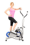 Full length portrait of a young woman posing on a cross trainer. Fitness machine, isolated on white background royalty free stock photos