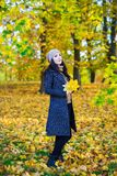 Full length portrait of young woman posing with yellow leaves in Stock Photography