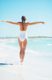 Full length portrait of young woman rejoicing on beach Stock Photo