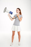 Full length portrait of a young woman shouting in megaphone. Isolated on a white background Royalty Free Stock Image