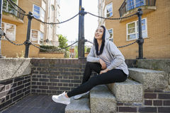 Full length portrait of young woman sitting on stairs Royalty Free Stock Photography