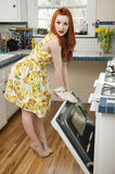 Full length portrait of a young woman standing by an open oven Royalty Free Stock Images