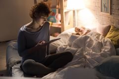 Mother Reading Bedtime Story to Child. Full length portrait of young women sitting on bed reading bedtime story to child sleeping next to her in dim lamplight Stock Photography