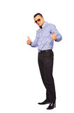 Full length portrasit of stylish young man thumbs up white backg Royalty Free Stock Images