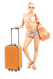 Full length portriat of a female tourist in bikini with a suitca Royalty Free Stock Image