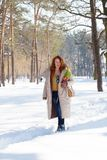 Charming red haired woman having a stroll in winter forest stock photos