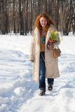 Joyful red haired woman walking along winter footpath royalty free stock images
