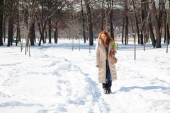Full length of positive woman standing on winter footpath royalty free stock image