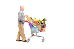 Full length potrait of a gentleman pushing a shopping cart full. Of groceries isolated on white background royalty free stock image