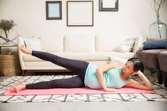 Pregnant Mother Doing Side Leg Lifts On Fitness Mat At Home royalty free stock image