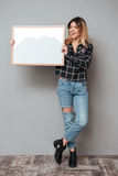 Full length of a pretty smiling woman holding blank board. Full length portrait of a pretty smiling woman holding blank board and looking away  over grey Royalty Free Stock Photography