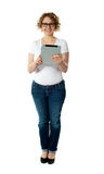Full length of pretty woman holding tablet pc. Full length of pretty woman holding new electronic tablet pc isolated over white background Royalty Free Stock Photos