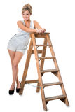 Full length of pretty young blonde, in overalls, resting on old Royalty Free Stock Image