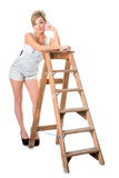 Full length of pretty young blonde, resting on old stepladder Royalty Free Stock Photography