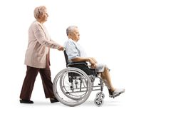 Elderly woman pushing an elderly male patient in a wheelchair stock images