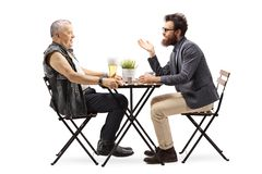 Mature man in a leather vest drinking beer at a table and talking with a young bearded man stock photography