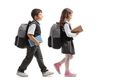 Full length profile shot a schoolboy and a schoolgirl with backpacks and books walking. Isolated on white background royalty free stock photography