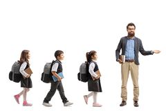 Full length profile shot of schoolchildren walking in a line and a teacher gesturing welcome with his hand and looking into the. Camera isolated on white royalty free stock images