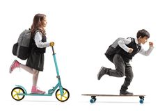 Full length profile shot of a schoolgirl riding a scooter and a. Schoolboy riding a longboard isolated on white background stock images