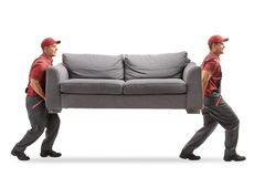 Movers carrying a couch. Full length profile shot of two movers carrying a couch isolated on white background stock image