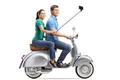 Full length profile shot of young couple taking selfie on a vintage motorbike. Isolated on white background stock photography