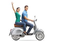 Full length profile shot of young male and female riding on a vintage motorbike, the girl waving. Isolated on white background royalty free stock image