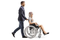 Young man pushing a young woman in a wheelchair. Full length profile shot of a young men pushing a young women in a wheelchair isolated on white background stock photos