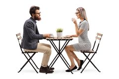 Young man and woman drinking coffee at a table stock photos