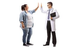 Young woman high-fiving a doctor. Full length profile shot of a young women high-fiving a doctor isolated on white background stock photo