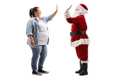 Young woman high-fiving Santa Claus. Full length profile shot of a young women high-fiving Santa Claus isolated on white background royalty free stock photo