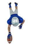 Full length rear view of American football player reaching towards ball Stock Photo