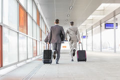 Full length rear view of businessmen with luggage running on railroad platform Stock Images