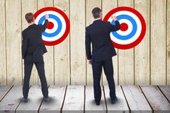 Full length rear view of businessmen setting targets on wooden wall. Digital composite of Full length rear view of businessmen setting targets on wooden wall Royalty Free Stock Photography