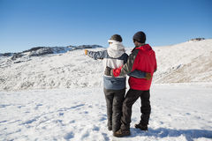 Full length rear view of a couple standing on snow Royalty Free Stock Photography