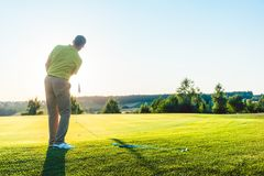 Experienced male golfer hitting the golf ball towards the cup. Full length rear view of an experienced male golfer hitting the golf ball towards the cup on the stock photography