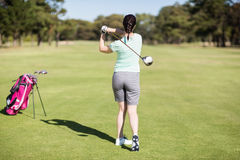 Full length rear view of golfer woman taking shot. While standing at golf course royalty free stock images