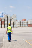 Full-length rear view of male worker walking in shipping yard stock image
