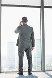 Full length rear view of mature businessman using cell phone white standing near window Stock Photo
