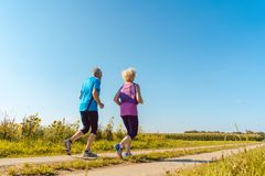 Two healthy senior people jogging on a country road in summer Royalty Free Stock Photos