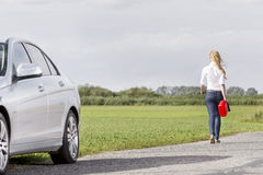 Full length rear view of woman carrying gas can leaving behind broken down car at countryside stock photos