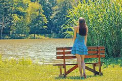 Full Length Rear View of a Woman Overlooking Calm Lake Royalty Free Stock Image