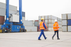 Full-length rear view of workers walking in shipping yard Stock Images
