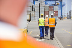 Full-length rear view of workers walking in shipping yard Stock Photo