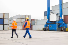 Full-length rear view of workers walking in shipping yard Royalty Free Stock Image