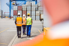 Full-length rear view of workers walking in shipping yard Royalty Free Stock Photography
