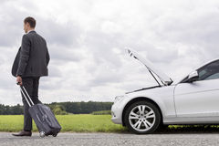 Full length rear view of young businessman with luggage leaving broken down car at countryside Stock Photos
