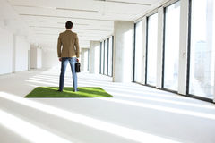 Full length rear view of young businessman standing on turf in empty office Royalty Free Stock Photography