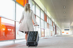 Full length rear view of young businesswoman with luggage rushing in railroad station Stock Photos