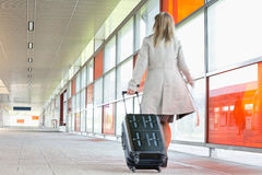 Full length rear view of young businesswoman with luggage rushing in railroad station Stock Image